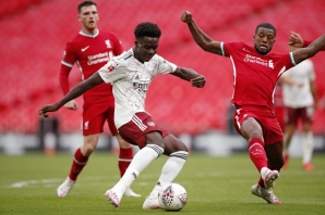 FILE: Arsenal's English striker Bukayo Saka (C) vies for the ball against Liverpool's Dutch midfielder Georginio Wijnaldum (R) during the English FA Community Shield football match between Arsenal and Liverpool at Wembley Stadium in north London on August