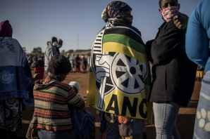 A woman wearing a blanket printed with the logo of South African ruling party African National Congress (ANC) queues with residents at a football field in the early morning during a distribution of hampers, masks, soap and sanitiser organised by different charities at the Iterileng informal settlement near Laudium, Pretoria, on May 20, 2020.