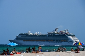 A cruise ship sails in the background as people relax in Miami Beach, Florida on July 2, 2020. Florida on Thursday reported a record of more than 10,000 new coronavirus cases, as it struggles to rein in the virus's spread, blamed in part on young people congregating in the US state.