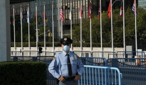 File: A UN police officer stands at an empty entrance at the United Nations during the 75th General Assembly of the United Nations which will be mostly virtual due to the COVID-19 pandemic in New York. (TIMOTHY A. CLARY / AFP)