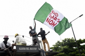 A protester waves the Nigerian national flag while gathering with other protesters to barricade the Lagos - Ibadan expressway