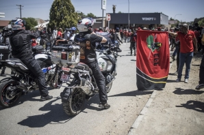 A member of the Economic Freedom Fighters (EFF) (R), points a flag at a biker that is taking part in a demonstration against farm attacks in Senekal, on October 16, 2020, ahead of the appearance of suspects in the Senekal Magistrates Court for the murder case of 22-year-old farm manager Brendin Horner.