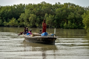 Fishermen ride a boat past a mangrove forest at Kainri Creek located in the Arabian Sea off the coast of Karachi.