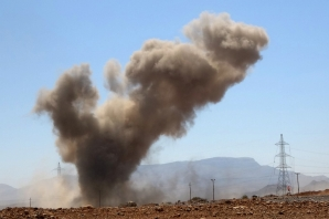 "A smoke plume rises following an explosion as forces loyal to Yemen's Saudi-backed government clash with Huthi rebel fighters around the strategic government-held ""Mas Camp"" military base, in al-Jadaan area about 50 kilometres northwest of Marib in central Yemen, on November 22, 2020."