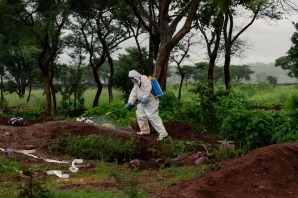 An undertaker in full body personal protective equipment (PPE) sprays disinfectant liquid around the grave of a person that passed away due to COVID-19 at Glen Forest cemetery in Harare