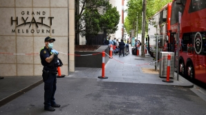 A policeman keeps watch as tennis players, coaches and officials arrive at a hotel in Melbourne on January 15, 2021, before quarantining for two weeks ahead of the Australian Open tennis tournament.