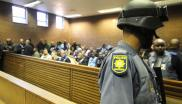 File: An armed police officer is seen at the Roodepoort Magistrates Court during the appearance and bail application of former ANC employee Errol Velile Present with three other cash-in-transit heist accused on July 31, 2018 in Johannesburg.