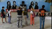 This picture taken on June 18, 2018 shows tourists taking pictures of a mural at the now-derelict ashram visited by the Beatles 50 years ago, in Rishikesh in northern India.