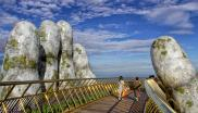 Nestled in the forested hills of central Vietnam two giant concrete hands emerge from the trees, holding up a glimmering golden bridge crowded with gleeful visitors taking selfies at the country's latest eccentric tourist draw.
