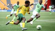Percy Tau (L) vies for the ball with Nigeria's Keneth Omerou during the African Cup of Nations qualifier match between South Africa and Nigeria.