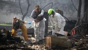 Rescue workers search an area where they discovered suspected human remains in a home destroyed by the Camp Fire in Paradise, California.