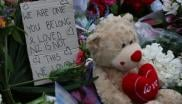 A note is seen beside floral tributes at a makeshift memorial for victims of the March 15 mosque attacks in Christchurch.