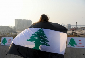 A woman, draped in a black-striped Lebanese flag, looks at the site of the massive explosion at Beirut's port area, during a demonstration to mark one month since the cataclysmic August 4 explosion that killed 191 people