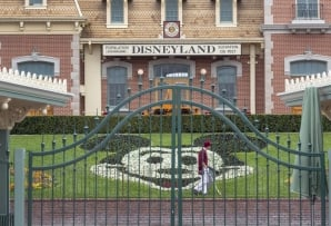 FILES: In this file photo taken on March 14, 2020 an employee cleans the grounds behind the closed gates of Disneyland Park on the first day of the closure of Disneyland and Disney California Adventure theme parks as fear of the spread of coronavirus con