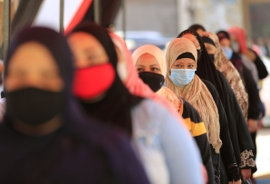 File: Egyptians wearing face masks against COVID-19 queue up to vote. (Khaled DESOUKI / AFP)