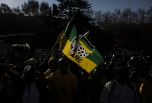 A man holds a flag of the South African ruling party African National Congress (ANC), as he gathers with supporters of former South African President Jacob Zuma outside House Hill building during the former South African president appearance at the Zondo Commission in Johannesburg, South Africa on July 15, 2019.