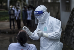 A health worker in Personal Protective Equipment (PPE) suit collects a swab sample from a man to test for the Covid-19 coronavirus at the department of medical research (DMR) in Yangon on October 8, 2020.