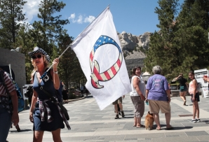A Donald Trump supporter holding a QAnon flag visits Mount Rushmore National Monument on July 01, 2020 in Keystone, South Dakota.