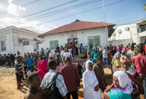More than a hundred people wait on the outskirts of the port of Pemba