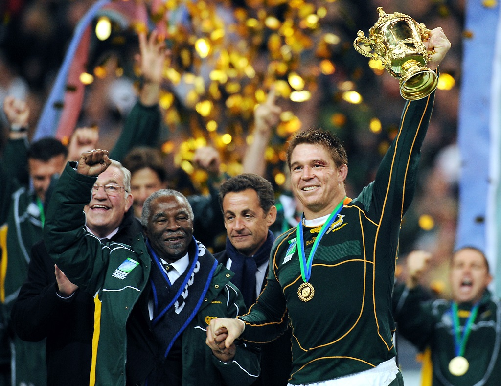Then Springbok captain John Smit holds the William Webb Ellis trophy as he shakes hands with then South African president Thabo Mbeki after the World Cup final match England vs. South Africa, 20 October 2007 at the Stade de France in Paris.